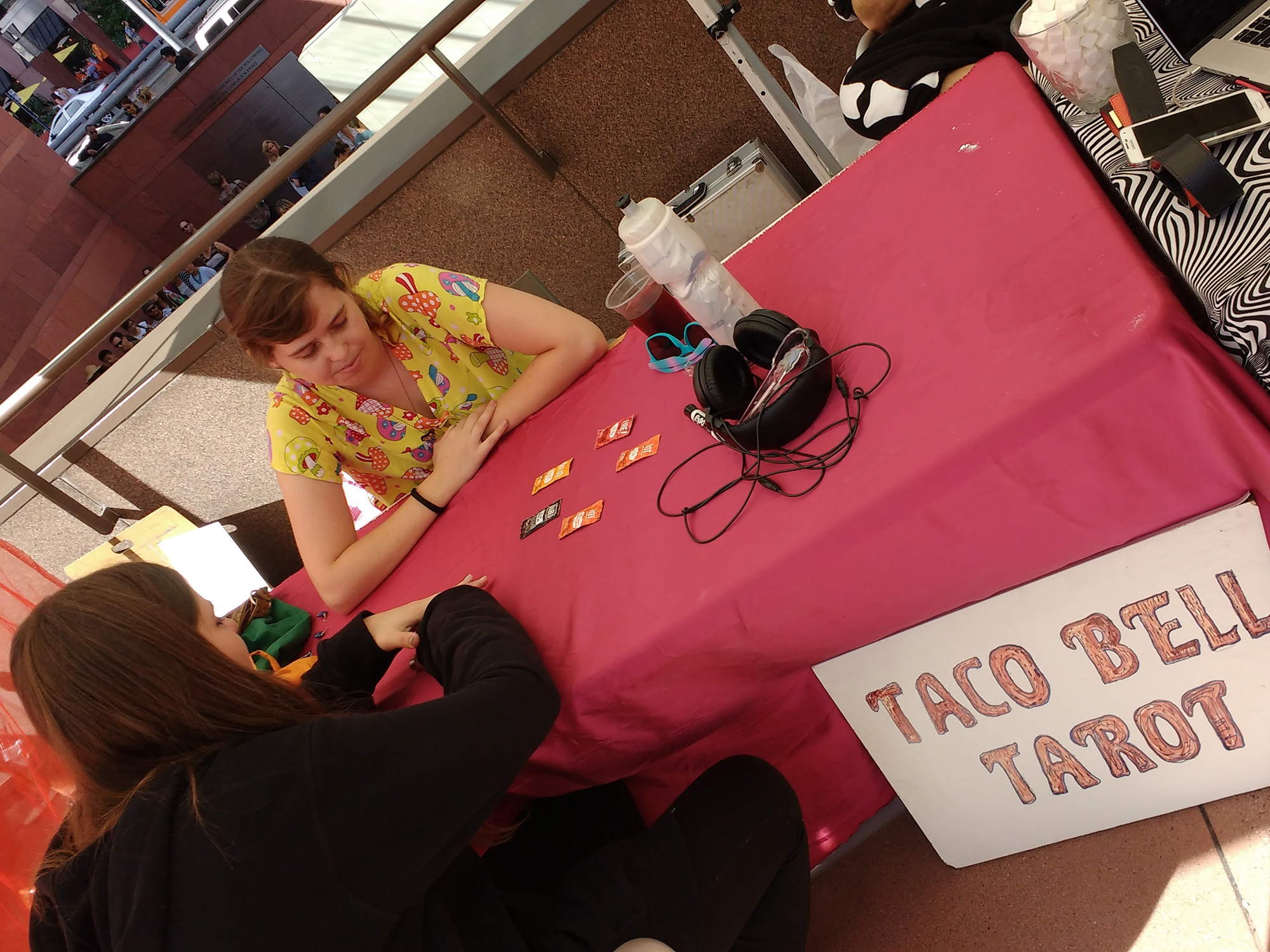 Two women seated across a table. One uses different Taco Bell sauce packets to do a Tarot reading for the other