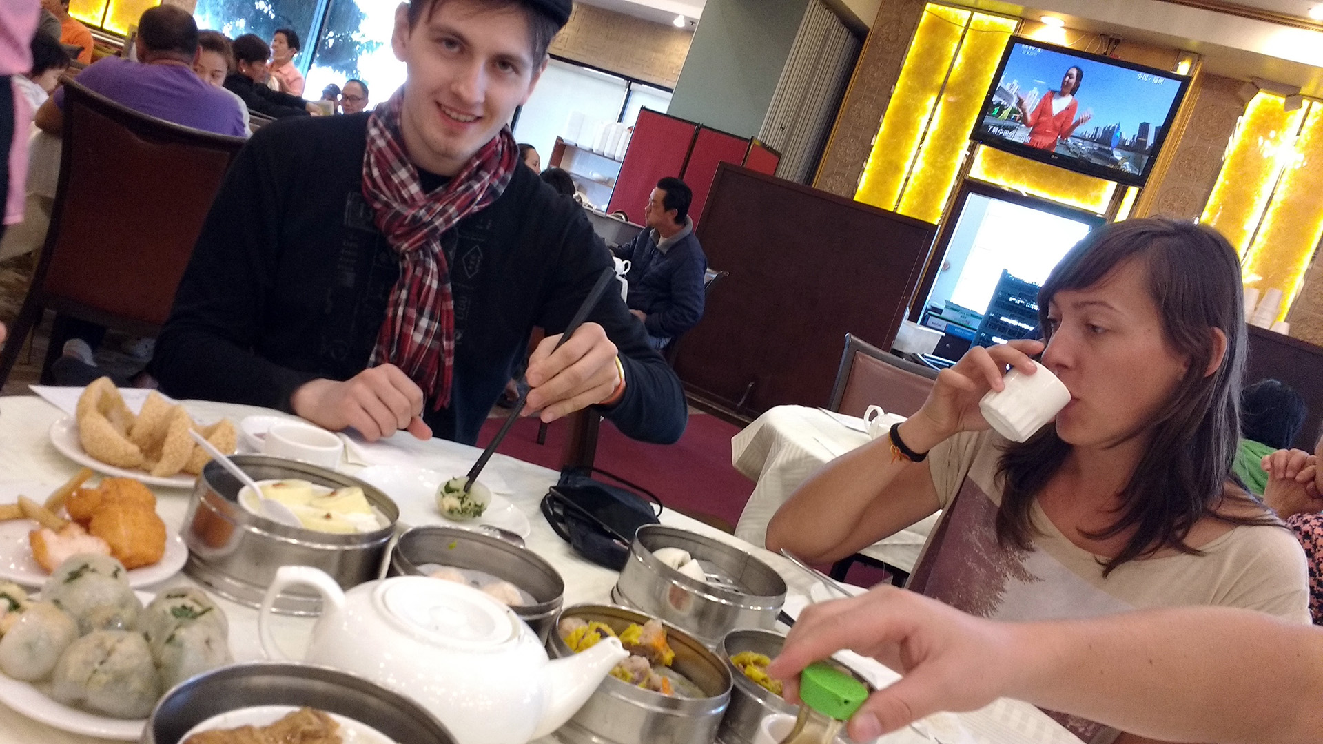 2 people seated at a table eating dim sum