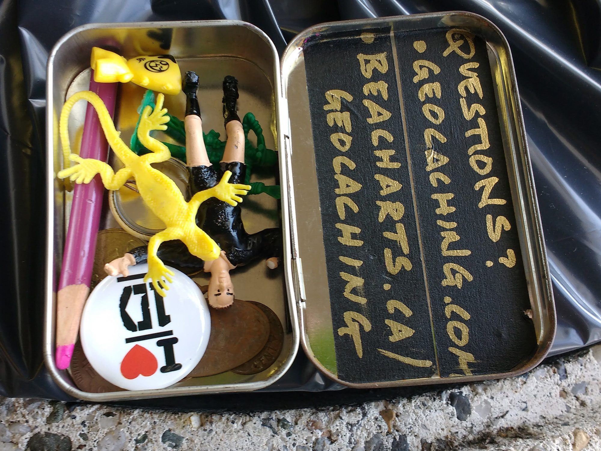 photo of the contents of a small geocache inside an Altoids tin