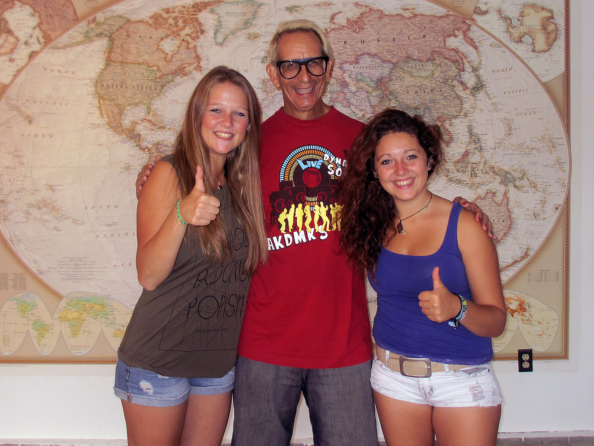 Stefanie, Glenn & Zeinab posing in front of a large world map