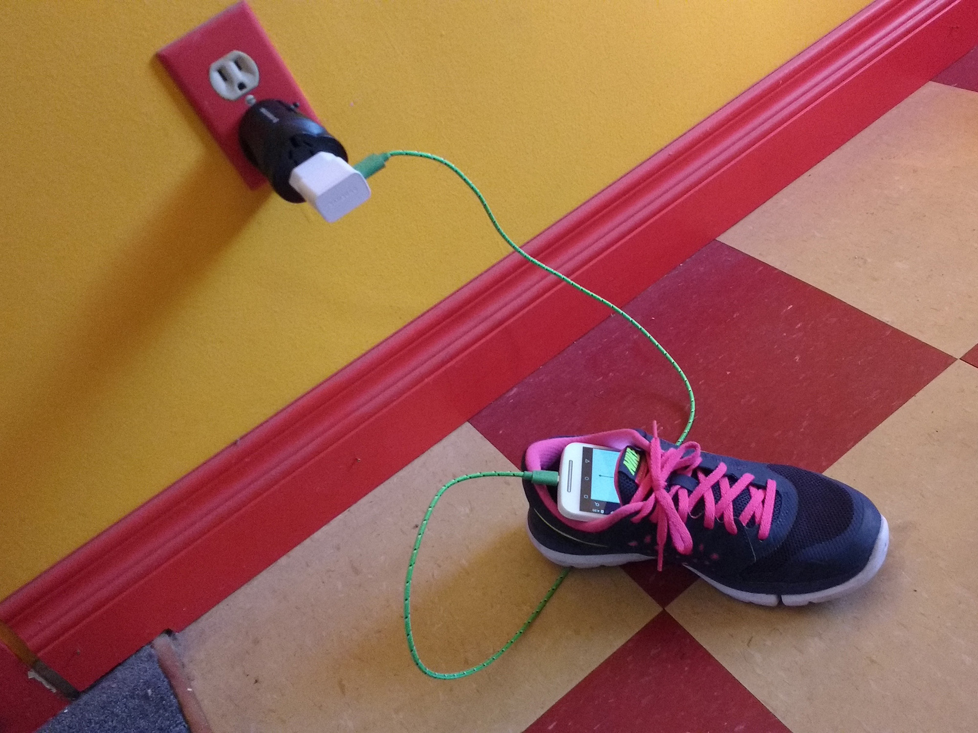 Image of USB-to-AC and European-to-American power adapters plugged into wall current and charging a phone which rests in a running shoe
