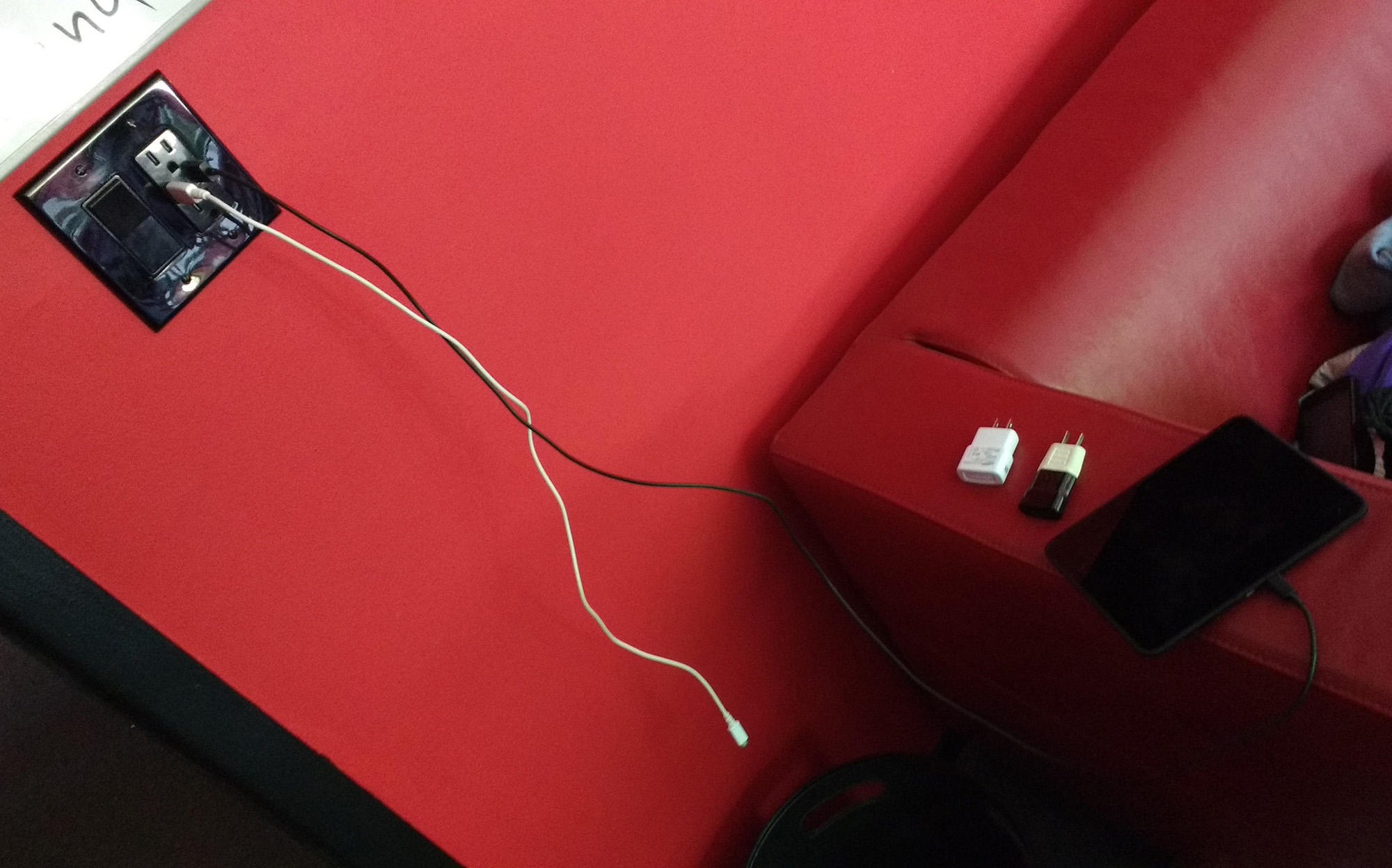 Image of power adapters set aside as a tablet plugs directly into USB wall power
