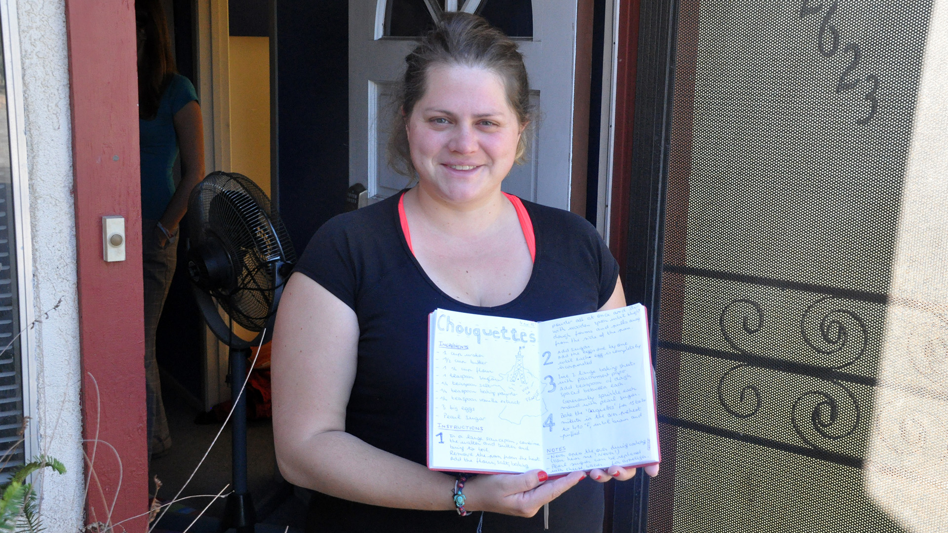 Cecile Barbot holding a journal that contains a hand-written recipe for Chouquettes