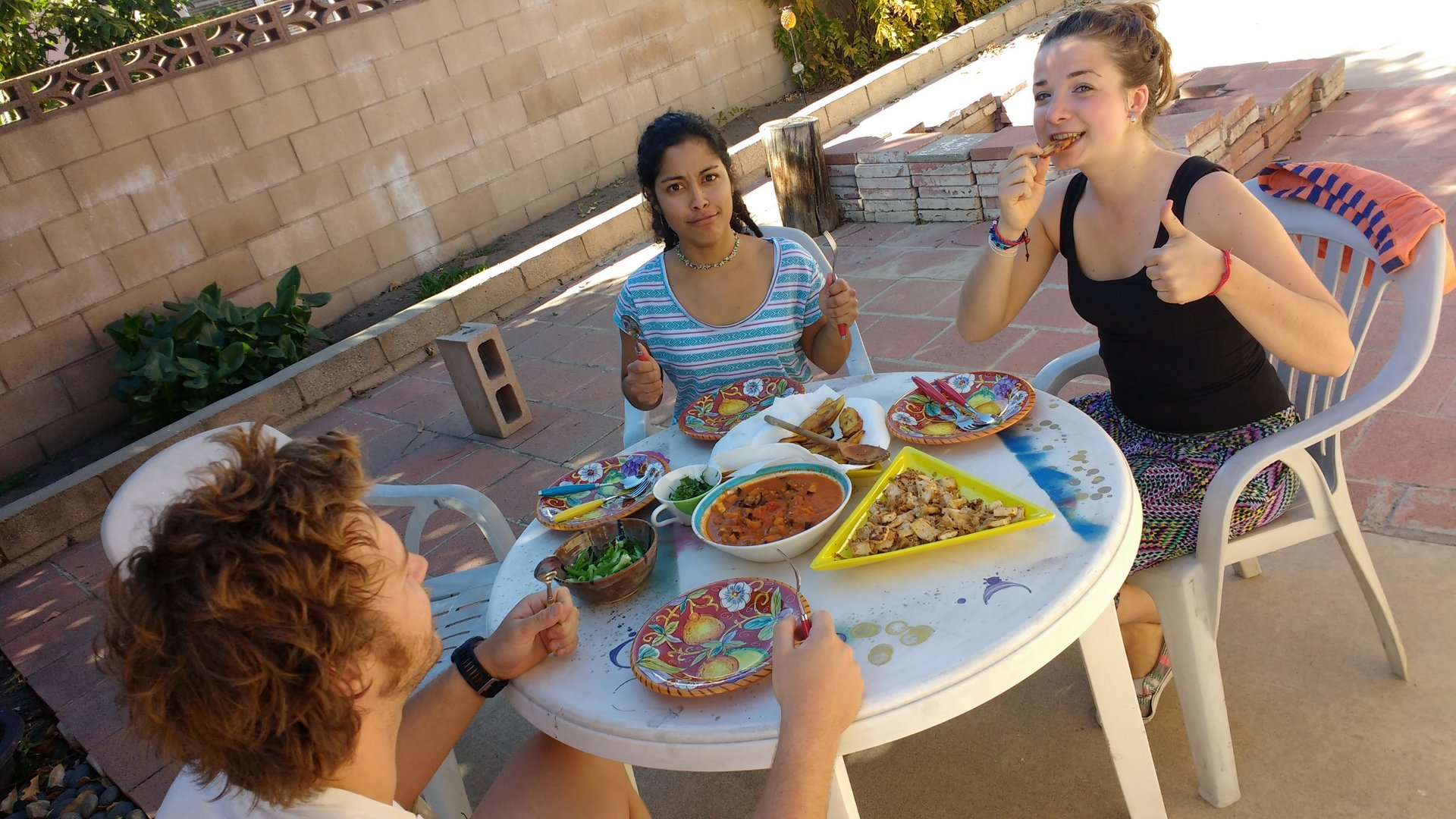 people sitting around a table and eating a meal