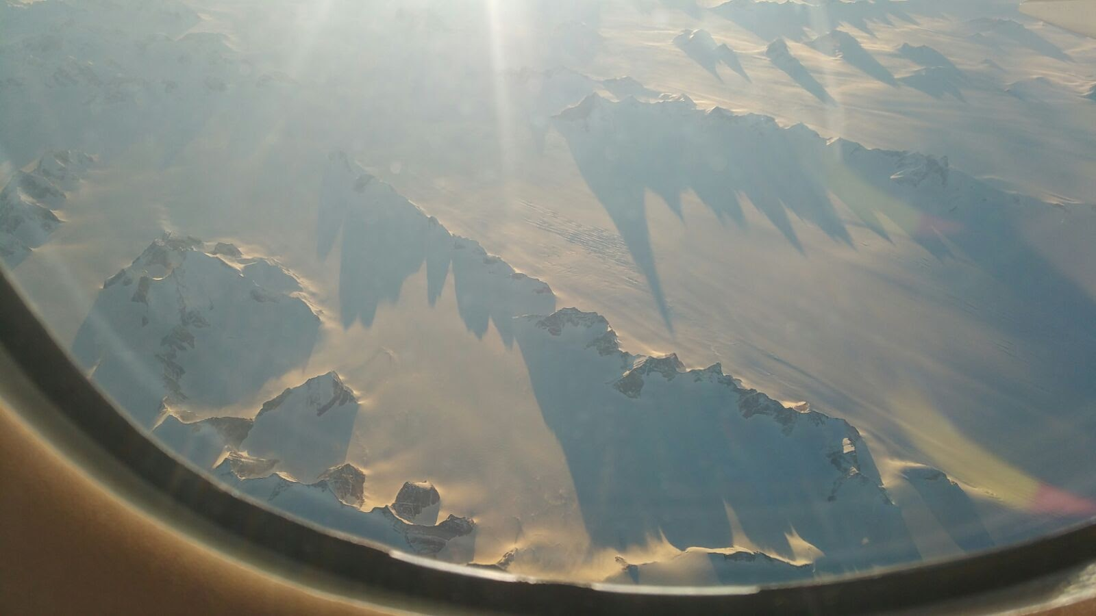Photo of ice-covered Greenland out an airplane window