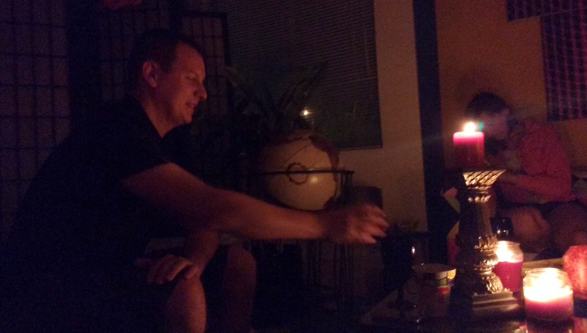 2 people drinking wine by candlelight