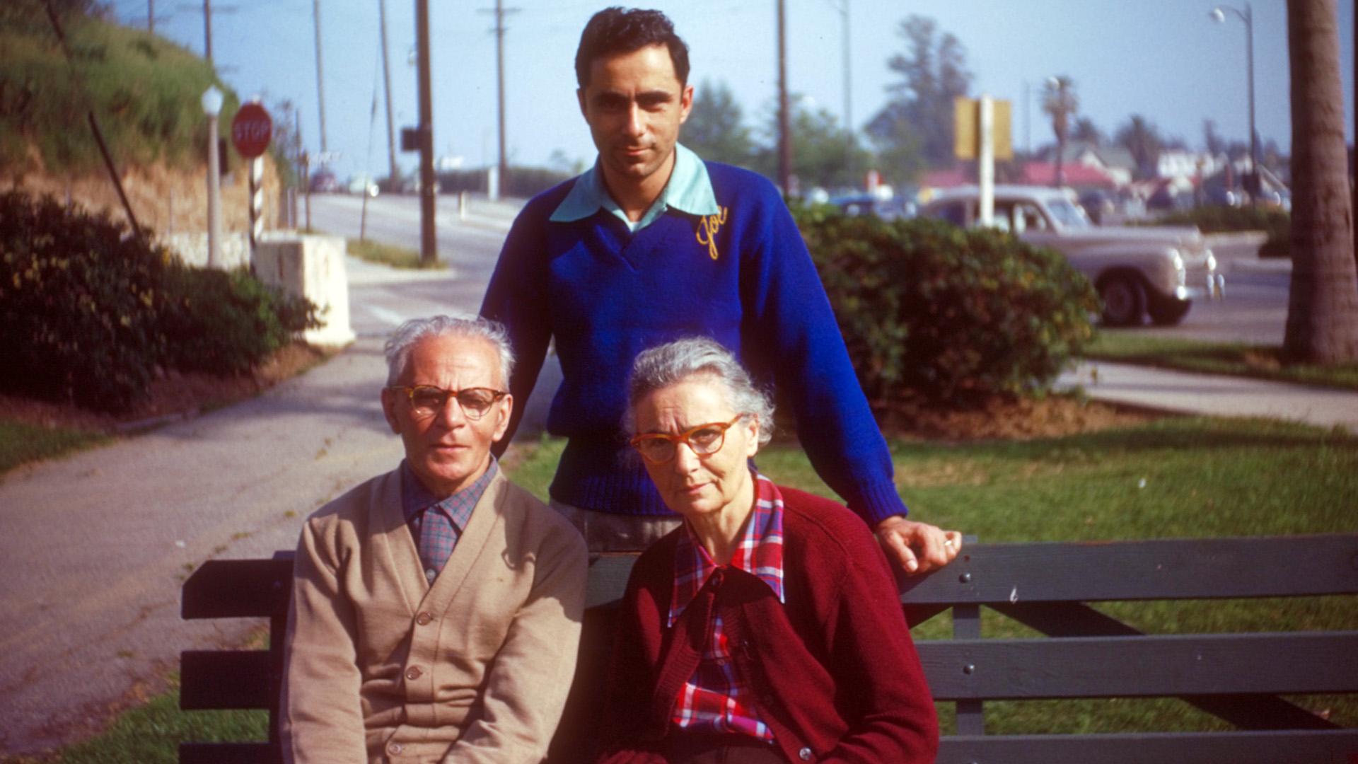 two senior citizens sitting on a park bench with their son standing behind them