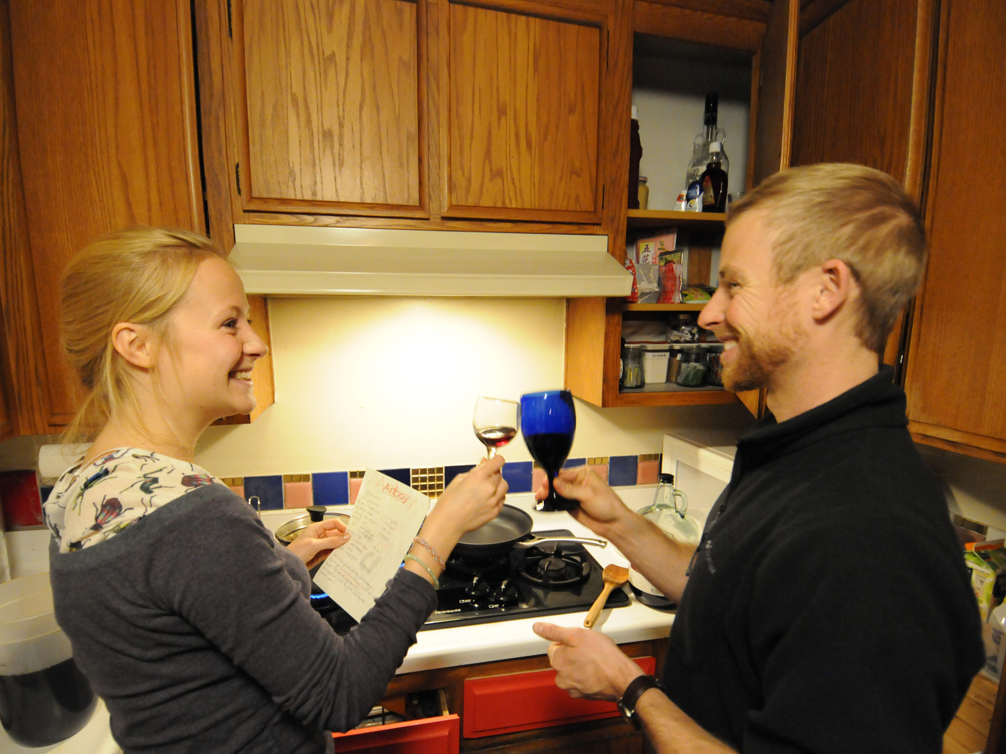 Bianca Golling & Mike Liggett clinking wine glasses in the kitchen