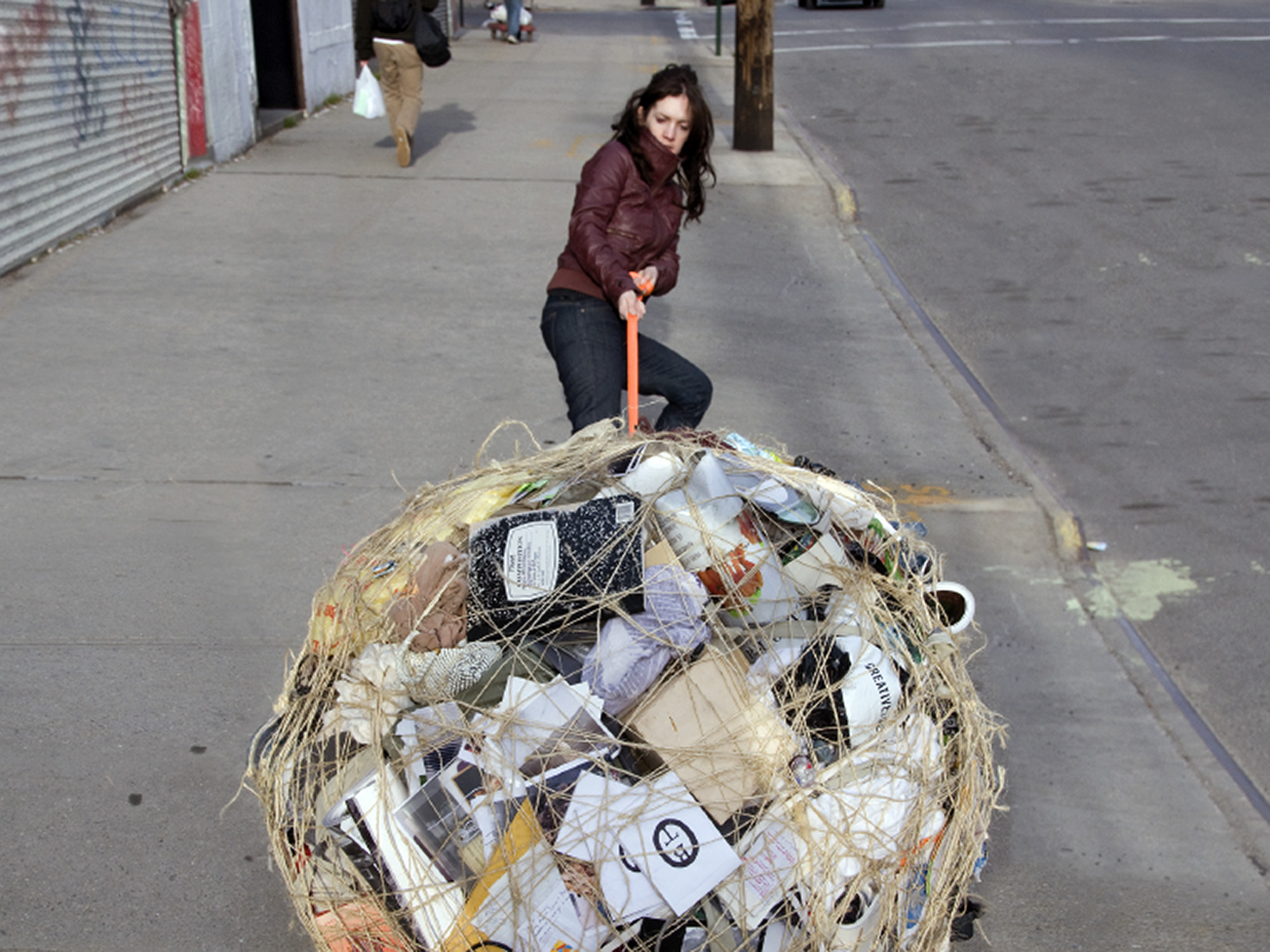 "c-print of Mary Mattingly pulling a large ball of ""stuff"""