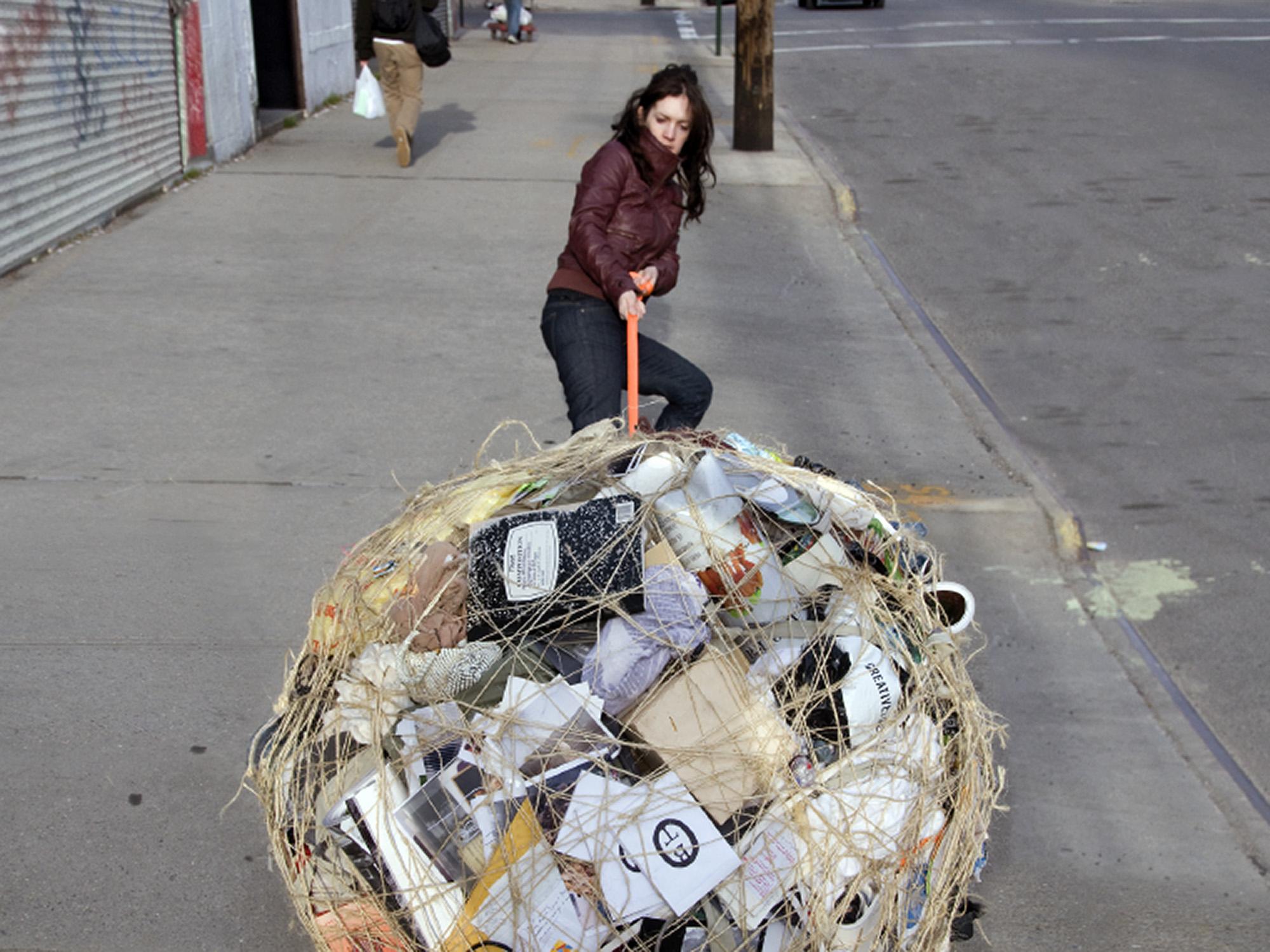 "c-print of Mary Mattingly pulling a large ball of ""stuff"""