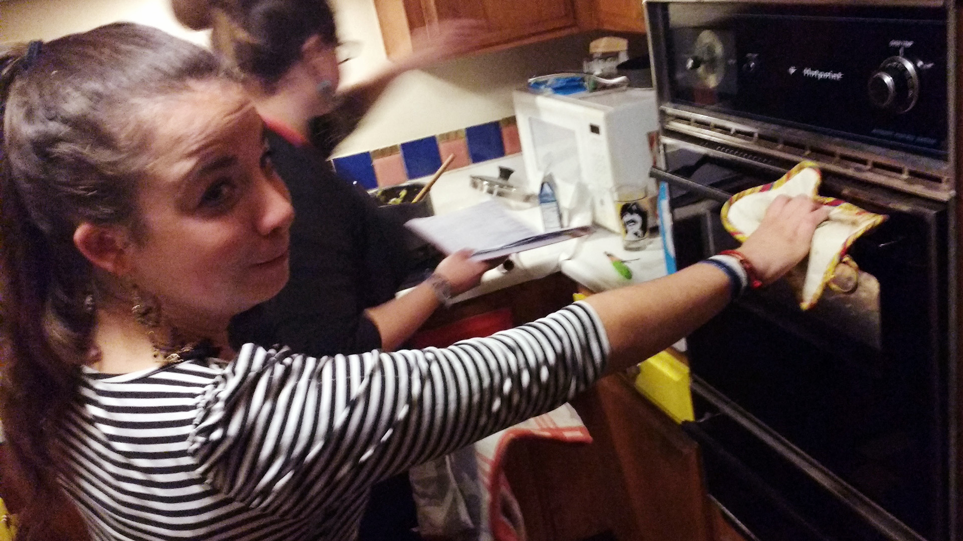 Terézia with her hand on the oven door about to open it, but with a look of apprehension on her face