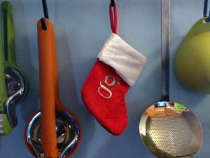 "kitchen tools hanging from the wall, including a tiny christmas stocking with a ""g"" on it"