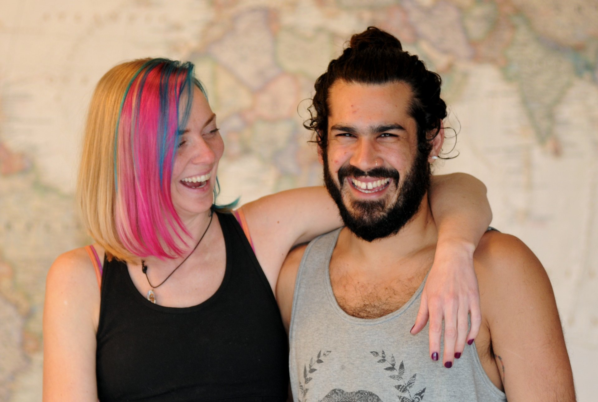Candi & Darich smiling in front of a large world map and showing Candi's new Pink & Blue hair color