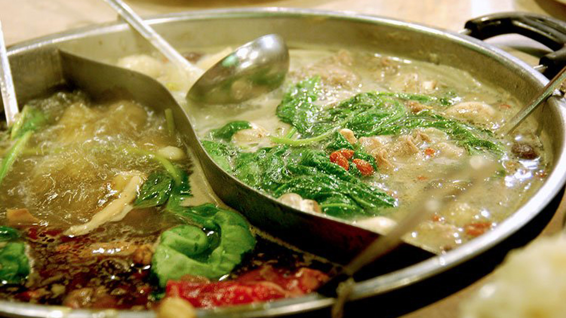 photo of a large hot pot divided into the shape of a yin-yang symbol
