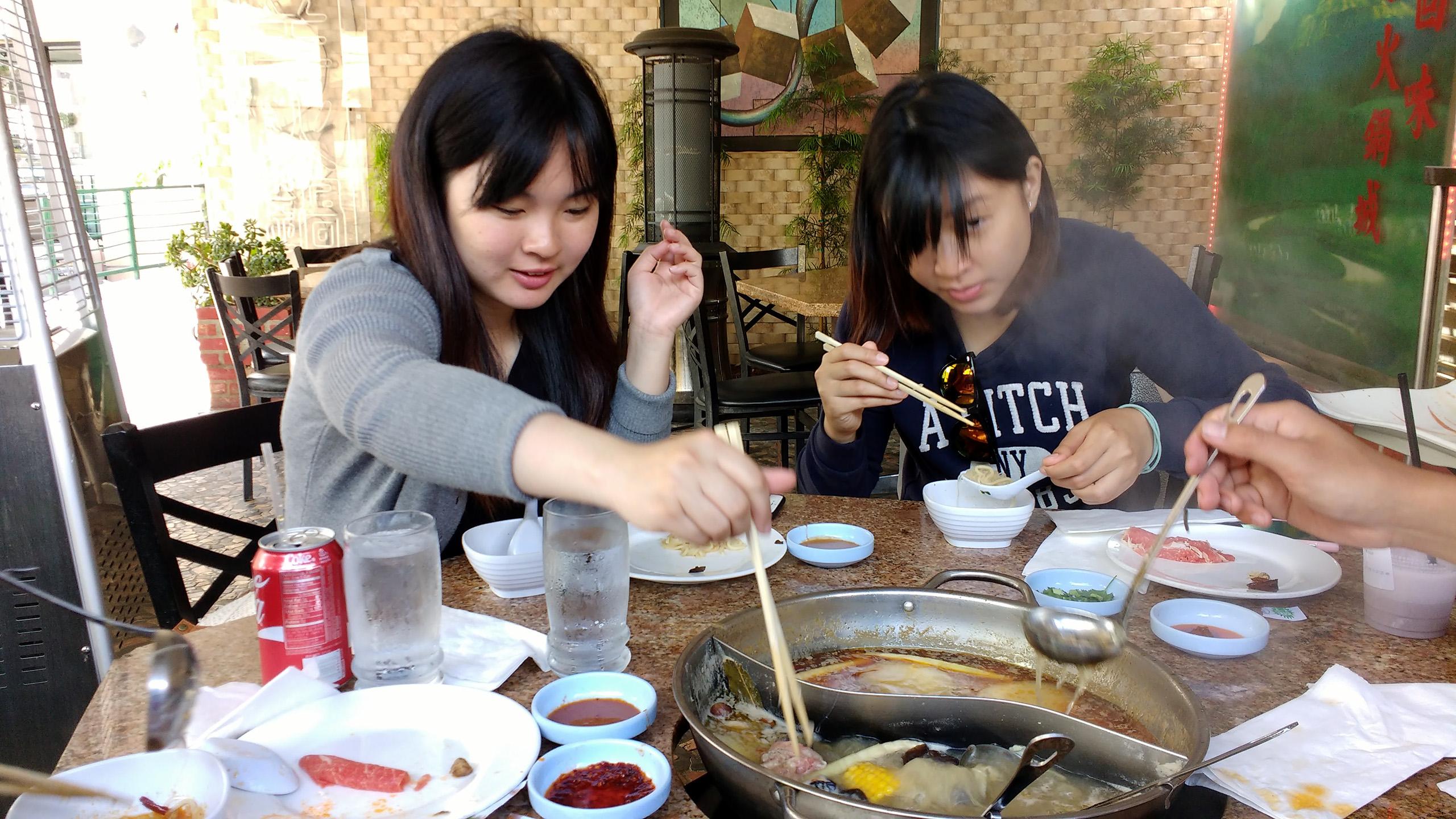 Joey reaches her chopsticks into the hot pot