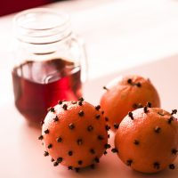 3 spiced oranges (oranges with cloves inserted in the skin) on a white table