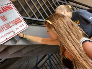 Stefanie Kuisle finding a small geocache behind a sign