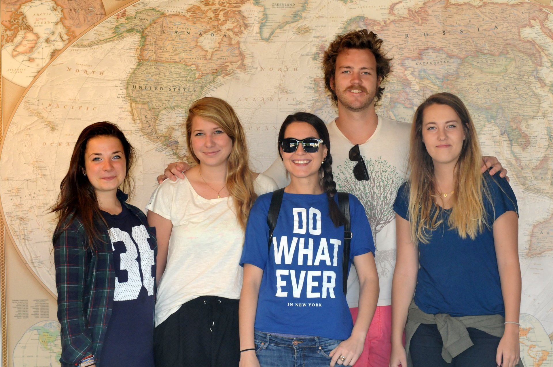 5 people standing in front of a large world map