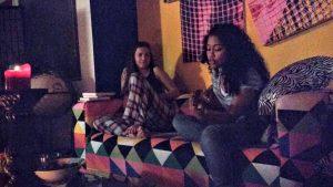 Terézia Ligačová & Eleonora Rey on a couch as Eleonora plays a Venezuelan Cuatro