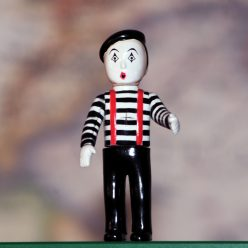 photo of a tiny toy figure of a mime in a beret and a striped shirt