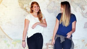 Hania & Husta standing in front of a 10-foot wide world map.