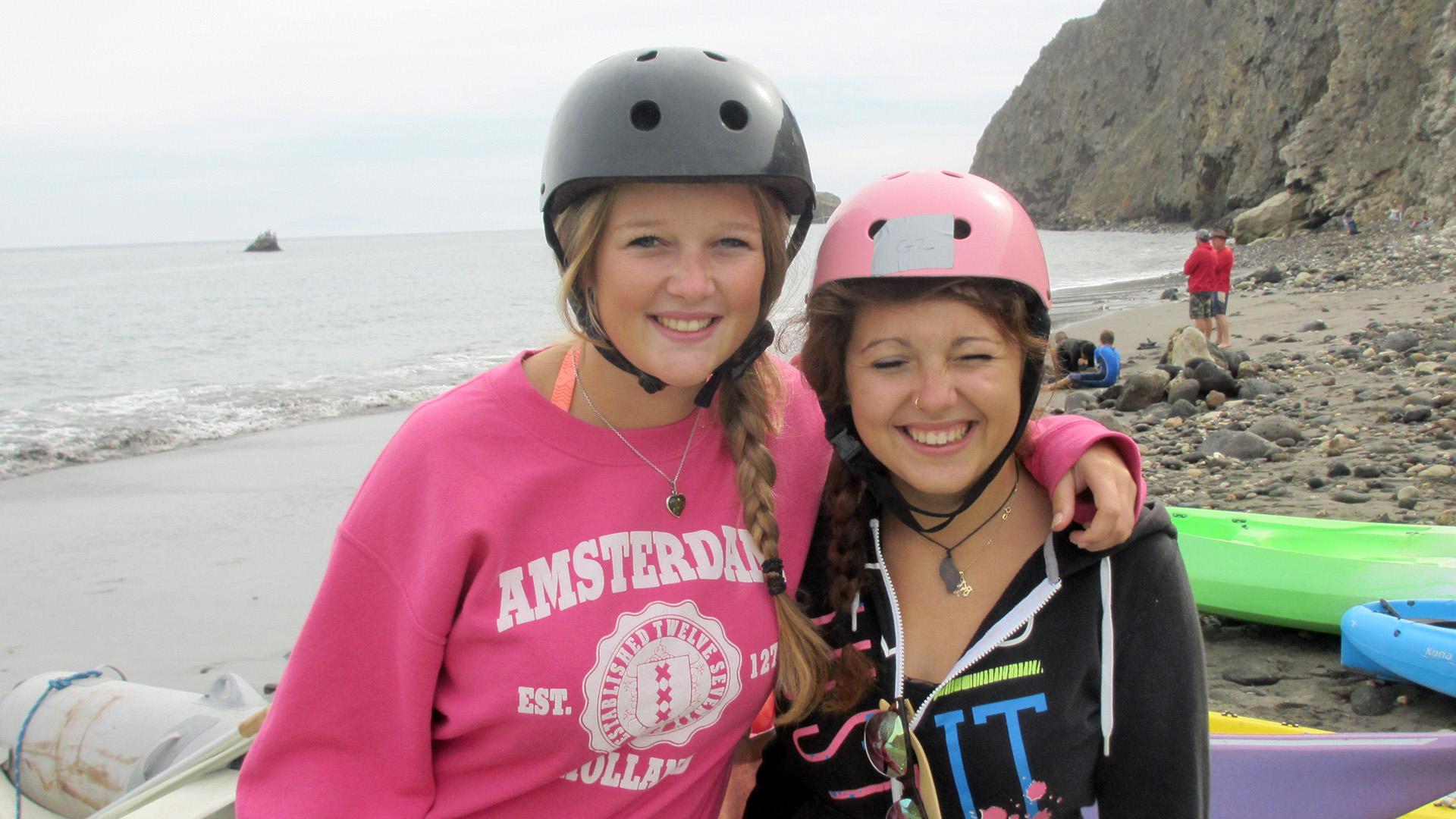 Stefanie in a pink sweatshirt & black helmet; Zeinab in a black sweatshirt & pink helmet.