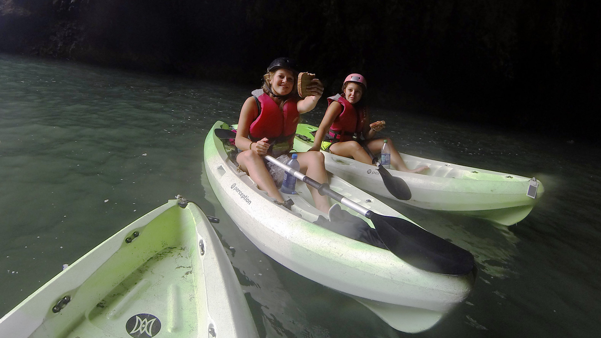 Stefanie and Zeinab eating sandwiches on kayaks inside a sea cave