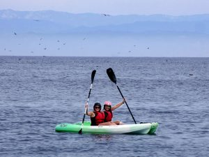 two kayakers surrounded by blue water and with hazy mountains behind them in the distance
