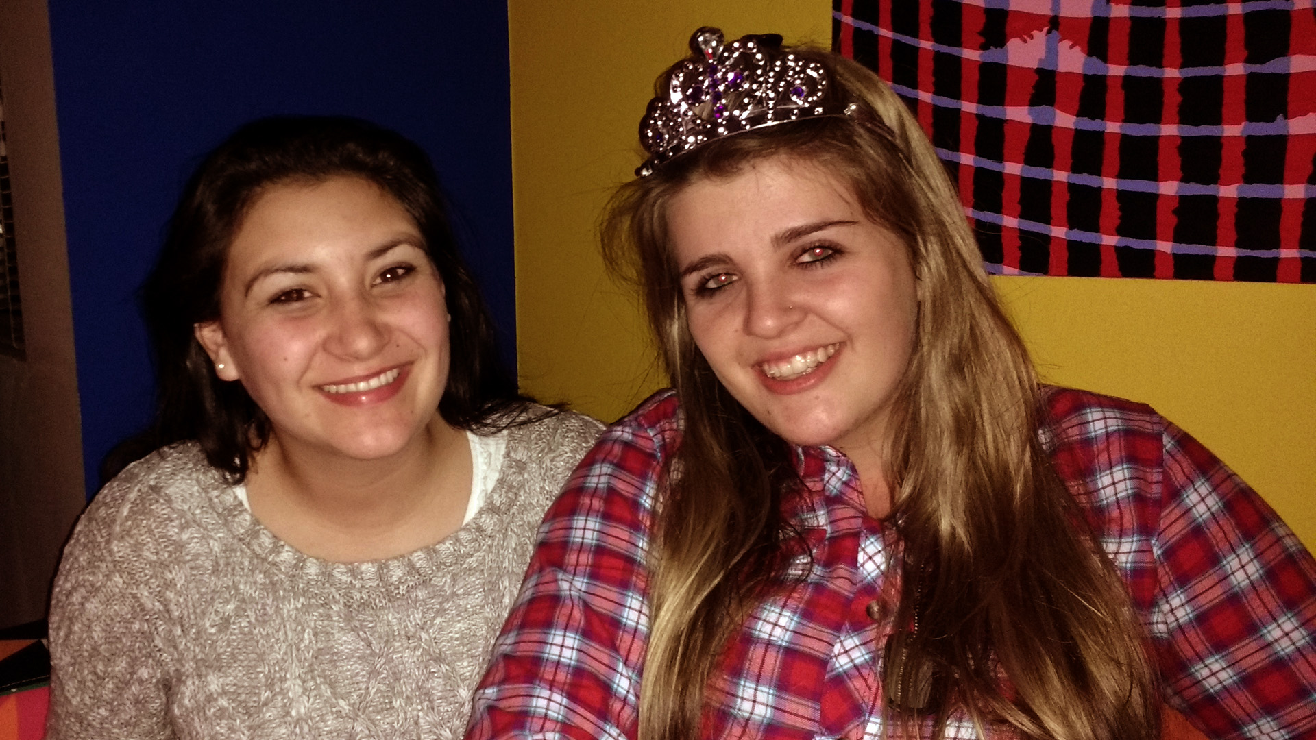 Celeste and Daleen sitting in the living room. Daleen wears a tiara.