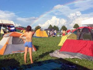 photo of tents on the grass with blue sky, puffy clouds, and a bright rainbow