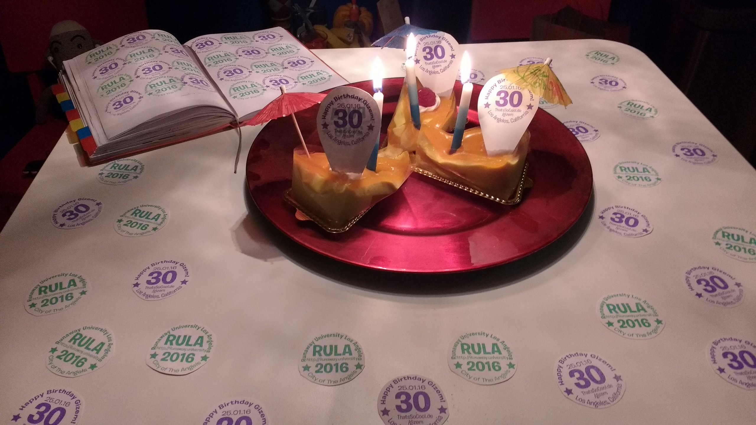 """3 slices of dessert on a table. The table is decorated with logos for """"RULA"""" and for """"Gizem's 30th Birthday"""""""