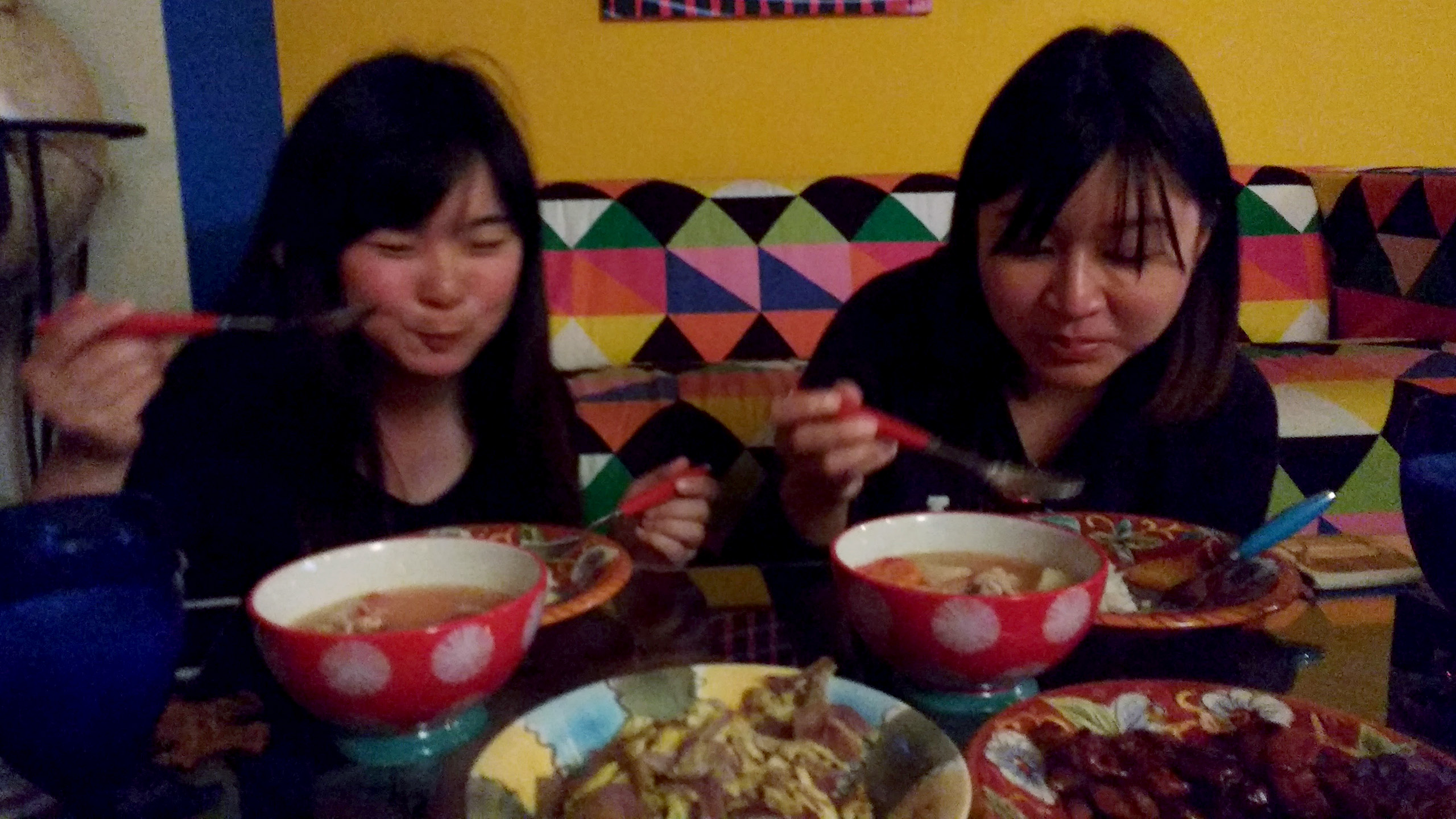 Joey & Ada sitting at a table covered with different dishes