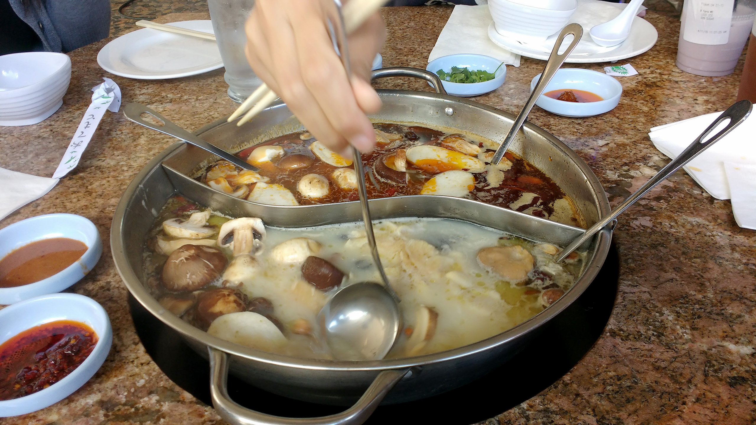 a large hot pot filled with ingredients in the center of a dining table. The hot pot is divided into two halves (mild and spicy) with a metal divider in the shape of a yin yang sign