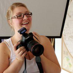 German beauty photographer Tamara Williams holding a camera and smiling big