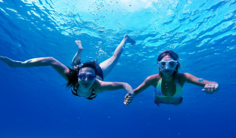 two people snorkeling and holding hands underwater