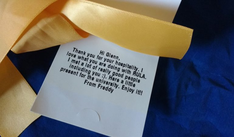 """gift tag on Freddy's Air Mattress bag with the text """"Hi Glenn, Thank you for your hospitality. I love what you are doing with RULA. I met a lot of really good people, including you. Here is a little present for the university. Enjoy it! From Freddy."""""""