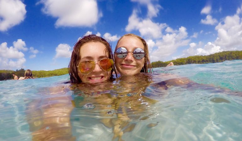 Hansine and a friend swimming with their heads above water and both smiling at the camera and wearing mirrored sunglasses